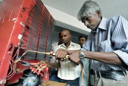 Dinesh (center) learns technique from Prabhu (right), a teacher of air conditioning and other electrical skills at a vocational training center run by Roofs for the Roofless in the city of Chennai, in the state of Tamil Nadu in southern India. Students John Joshuran and Dinesh look on.